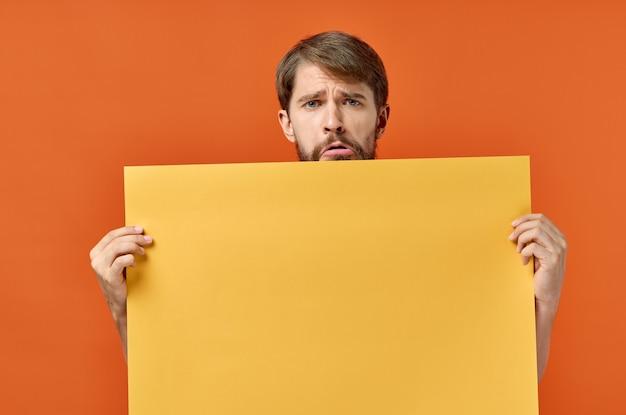 Werbeschild poster mann in der wand orange wand copy space. Premium Fotos