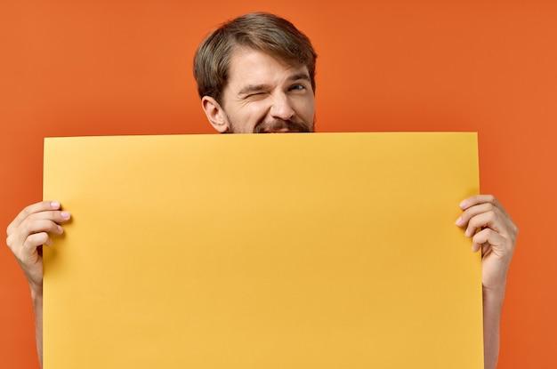 Werbeschild poster modell mann im hintergrund orange hintergrund copy space. hochwertiges foto Premium Fotos