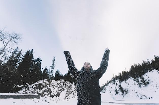 Werfender schnee der person auf waldhintergrund Kostenlose Fotos