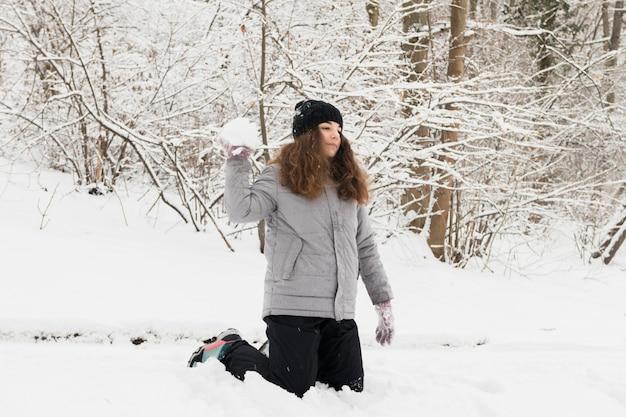 Werfender schneeball des mädchens im winterwald Kostenlose Fotos