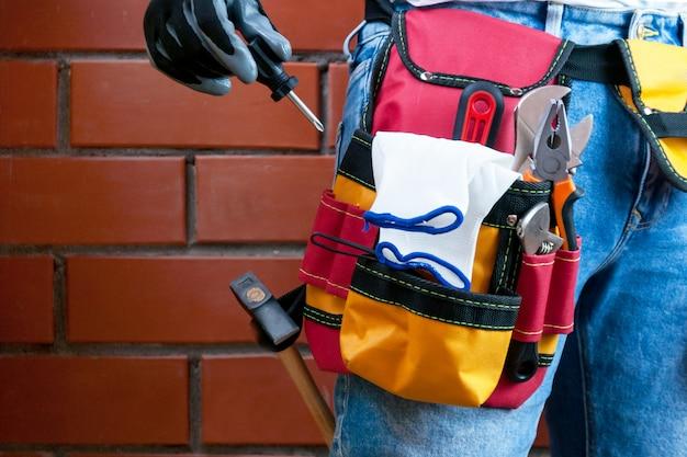 Werkzeuge im gurt für werkzeuge. der erbauer hält einen schraubenzieher. tiefenschärfe. Premium Fotos