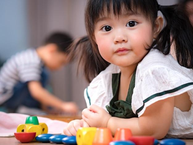 Wertvolles gesicht eines gesunden entzückenden asiatischen mädchens 2 jahre alt, legen sie sich auf den boden und spielen sie bunte hölzerne montessori sensorische spielzeuge. nettes kleines vorschulmädchen, geliebte tochter, kinderentwicklung Premium Fotos