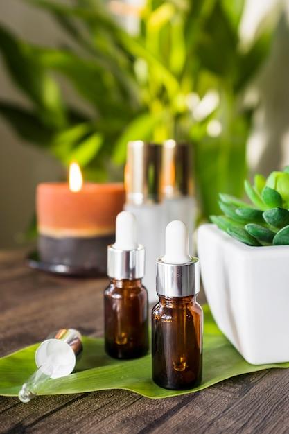Wesentliches aromaöl auf grünem blatt über der tabelle Kostenlose Fotos
