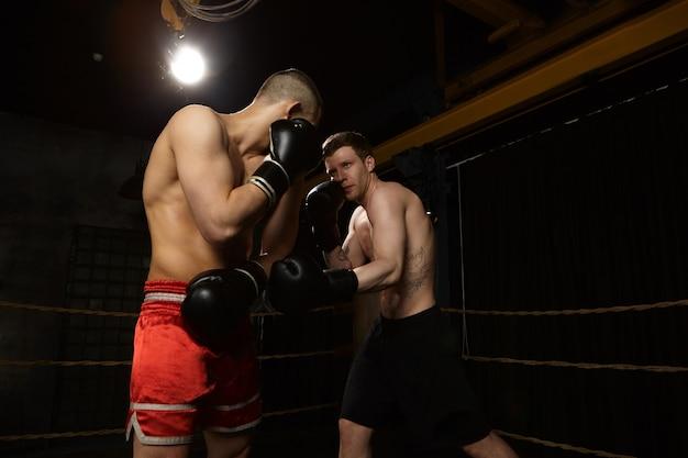 Wettbewerb, rivalität, menschen und sportkonzept. ernsthafter selbstbewusster junger kaukasischer mann mit tätowierungen und muskulösen armen, die gegen unerkennbaren mann in der roten hose kämpfen. zwei kämpfer boxen Kostenlose Fotos