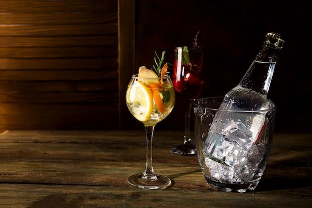 Whisky basierte cocktail mit glas eiseimer auf dunklem hölzernem backgorund Premium Fotos
