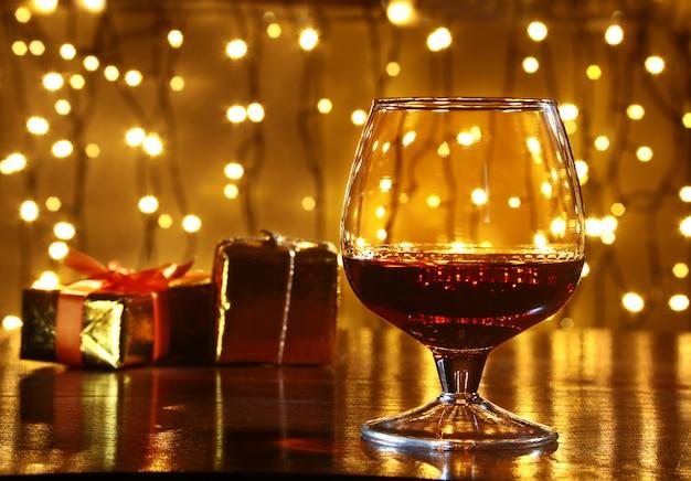 Whisky, kognak, weinbrand und geschenkbox auf holztisch. feieraufbau auf dem licht Premium Fotos