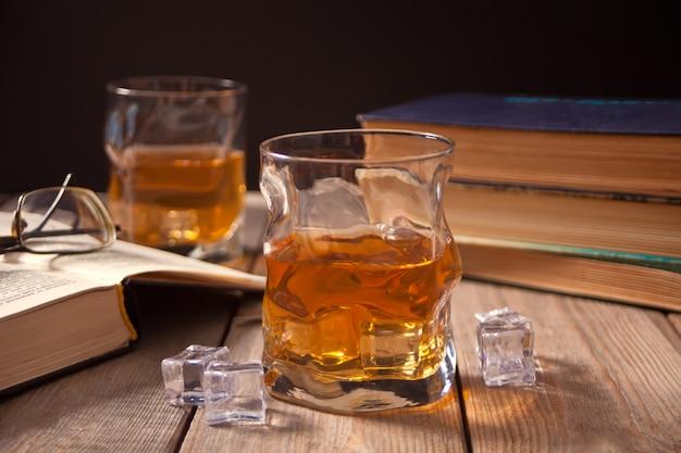 Whisky mit eis auf einem holztisch. in der nähe alte bücher. Premium Fotos