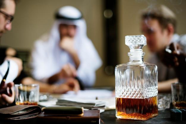 Whiskykaraffe mit geschäftsleuten im hintergrund Premium Fotos