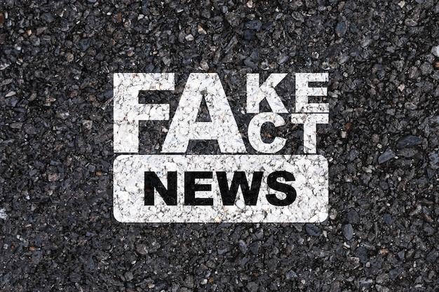 White fake and fact news-druckbildschirm auf asphaltbetonstraße. Premium Fotos