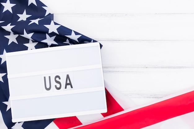 Whiteboard mit anmerkung usa, die auf amerikanischer flagge liegen Kostenlose Fotos