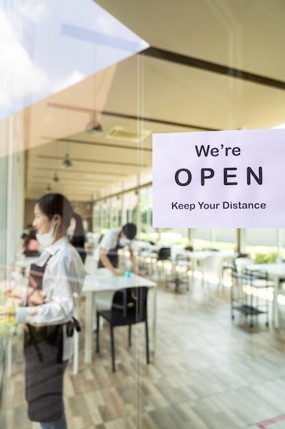 Wiedereröffnung der restaurantbeschilderung mit sozialer distanz für ein neues normales restaurant mit asiatischem kellner und kellnerin bereiten das restaurant vor der eröffnung vor. neues normales restaurant-lifestyle-konzept. Premium Fotos