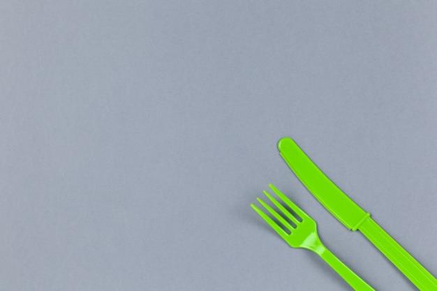 Wiederverwendbare recycelbare grüne gabel, messer aus maisstärke auf grauem hintergrund Premium Fotos