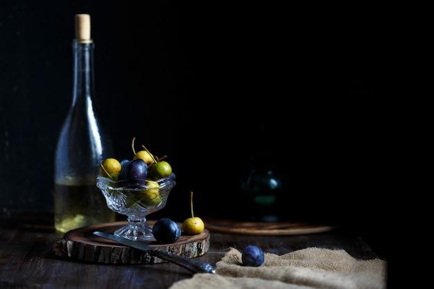 Wilde birne und pflaume in einer glasschüssel und eine flasche hausgemachter birnenwein Premium Fotos