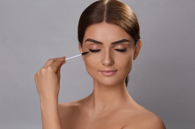 Wimperntusche. beauty make-up, frische, weiche haut und lange, schwarze, dicke wimpern, die wimperntusche mit kosmetikpinsel auftragen. wimpernverlängerung. falsche wimpern. Premium Fotos