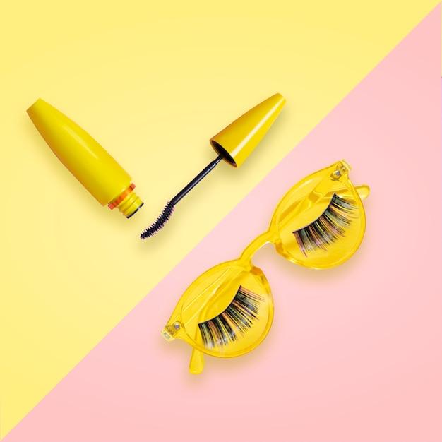 Wimperntusche in gelber tube mit offener bürste auf rosa und gelber sonnenbrille mit falschen wimpern. Premium Fotos
