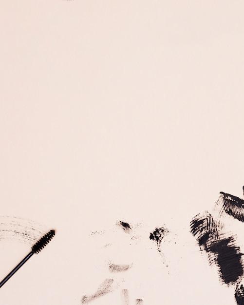 Wimperntuschenwimpernbürstenanschlag auf beige hintergrund Kostenlose Fotos