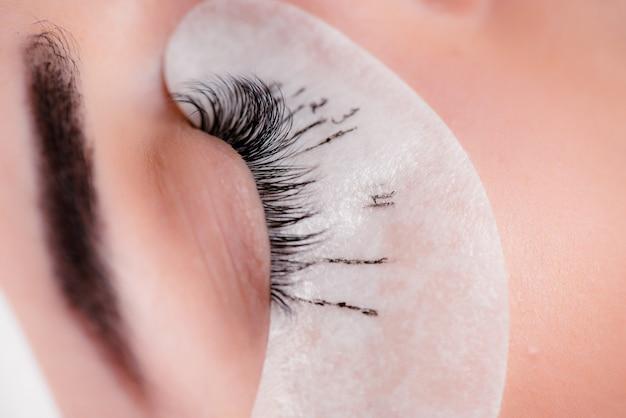 Wimpernverlängerung im schönheitssalon. training und markierung. Premium Fotos