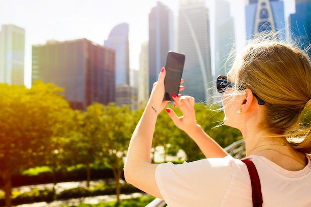 Wind weht die frau der frau, während sie bild von schönen wolkenkratzern auf ihrem iphone nimmt Kostenlose Fotos