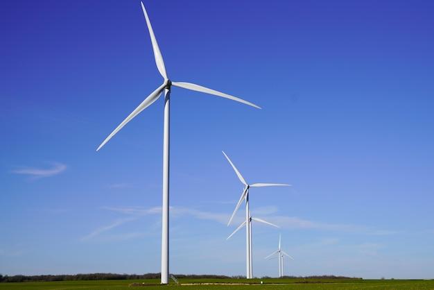 Windkraftanlagen und landwirtschaftliche felder am blauen himmel des sommertages Premium Fotos