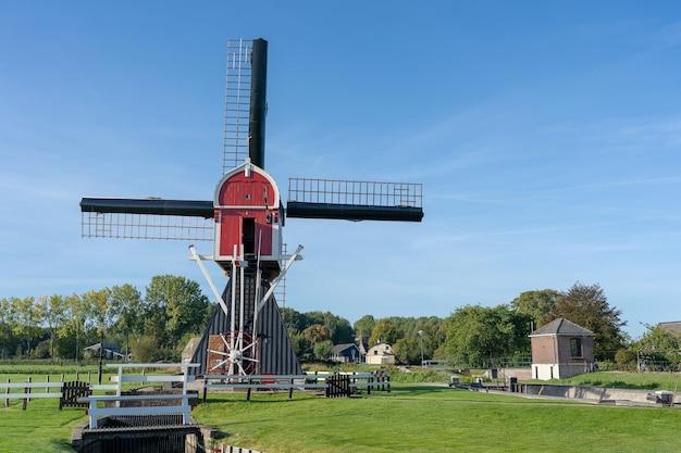 Windmühle unter einem klaren blauen himmel, umgeben von bäumen und vegetation Kostenlose Fotos