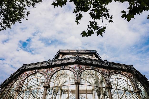 Windows des glaspalastes des retiro-parks in madrid, mit einer wand eines himmels mit wolken. Premium Fotos