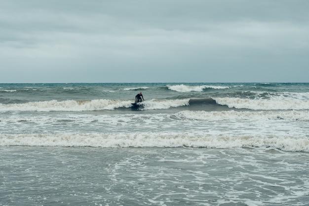 Windsurfer, die versuchen, kleine wellen während eines sturms zu reiten. Premium Fotos