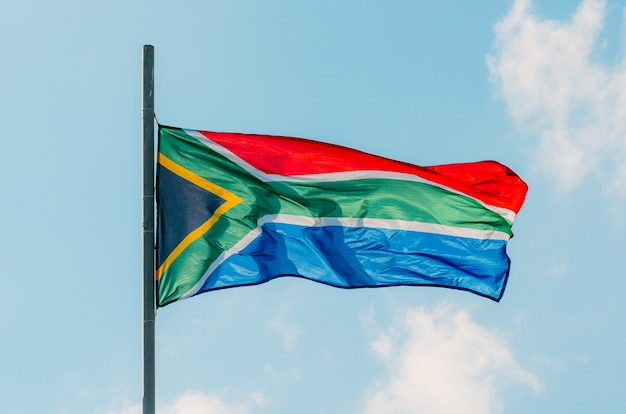 Winkende bunte südafrika-flagge auf blauem himmel. Premium Fotos