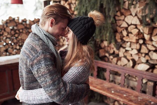 Winter, ferien, paare, weihnachten und leute - lächelnder mann und frau in den hüten und in schal, die über hölzernem landhaus und schnee umarmen Premium Fotos