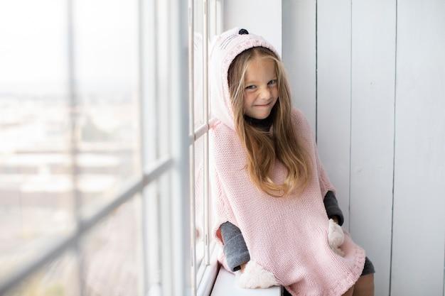 Winter gekleidetes kleines mädchen nahe bei einem fenster Kostenlose Fotos