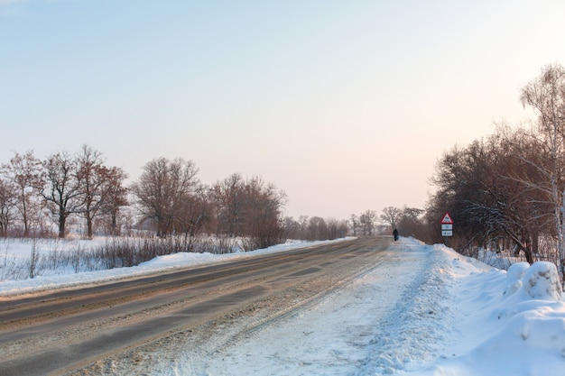 Winter schlecht geräumte straße. straße auf dem lande mit schnee übersät. winterlandschaft mit schneeverwehungen Premium Fotos