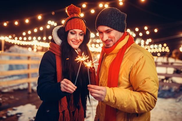 Winterabend, liebespaar mit wunderkerzen küssen Premium Fotos