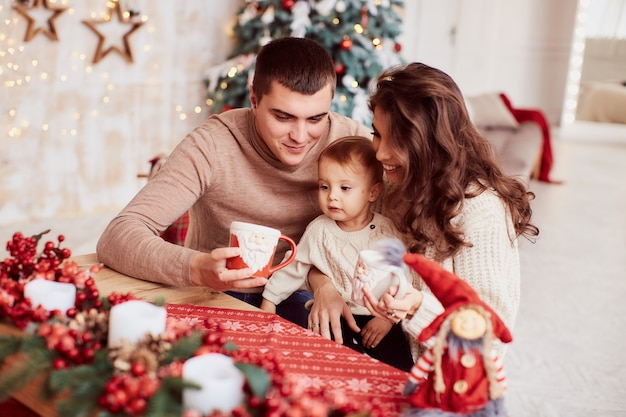 Winterferien dekorationen. warme farben. familienporträt. mama, papa und ihre kleine tochter Kostenlose Fotos
