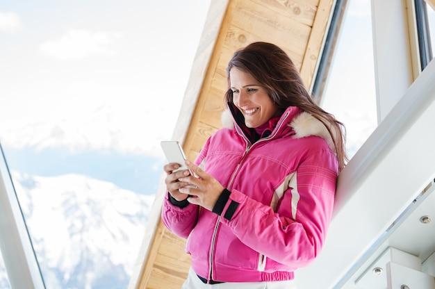 Winterfrau mit telefon in der lodge Premium Fotos
