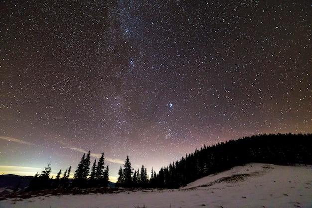 Wintergebirgsnachtlandschaftspanorama. helle konstellation der milchstraße im dunkelblauen sternenklaren himmel Premium Fotos