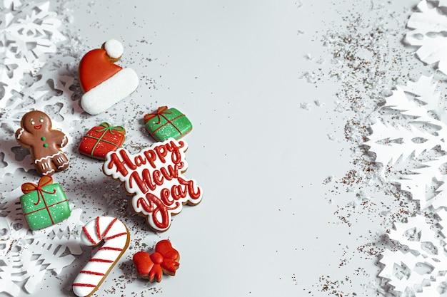 Winterhintergrund mit verziert mit glasurlebkuchen, schneeflocken und konfetti draufsicht. frohes neues jahr und weihnachtskonzept. Premium Fotos