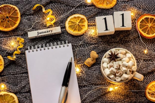 Winterkomposition. holzkalender 11. januar tasse kakao mit marshmallow, leerer offener notizblock Premium Fotos