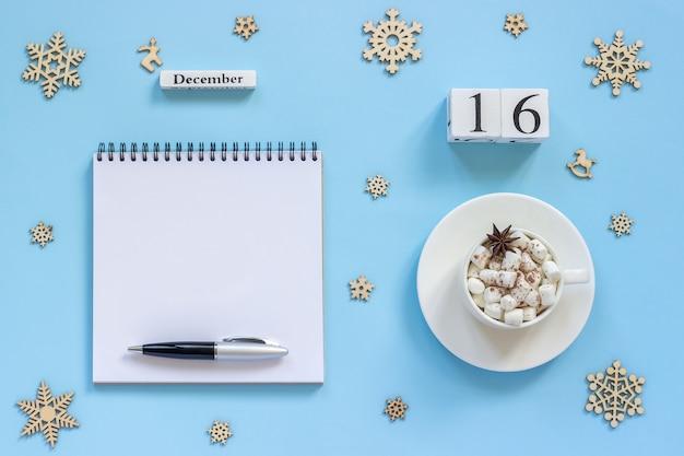 Winterkomposition. holzkalender 16. dezember tasse kakao mit marshmallow und sternanis Premium Fotos