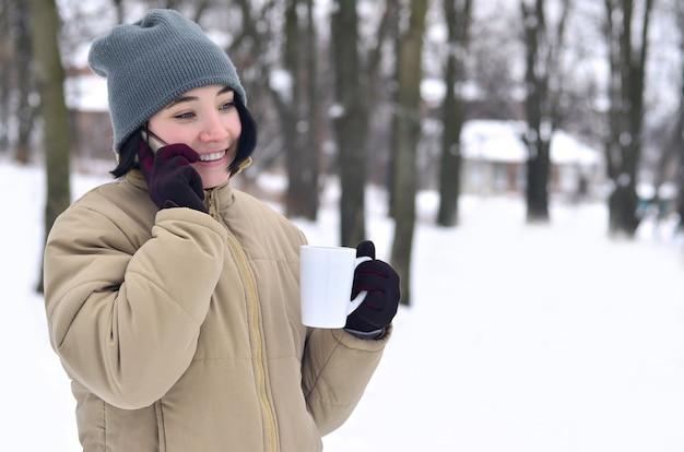Winterporträt des jungen mädchens mit smartphone und kaffeetasse Premium Fotos