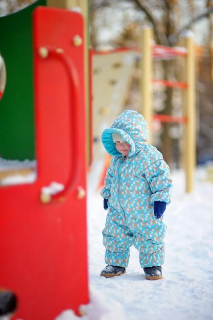 Winterporträt des schönen kleinkindjungen auf spielplatz Premium Fotos