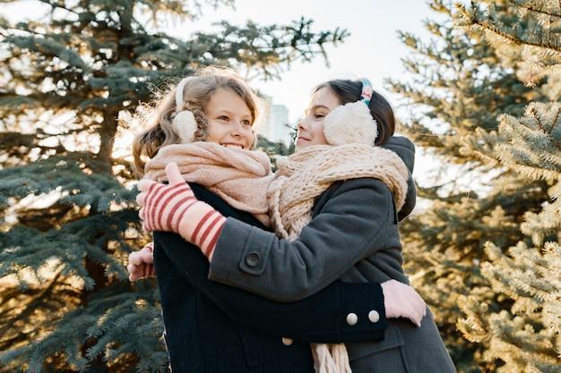 Winterporträt im freien von zwei kleinen mädchen Premium Fotos