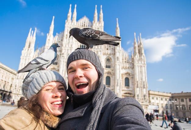 Winterreise- und urlaubskonzept - glückliche touristen, die ein selbstporträt mit lustigen tauben in nehmen Premium Fotos