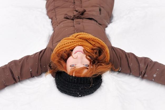 Winterspaß - schneeengel - junge schönheit, die im schnee spielt Premium Fotos