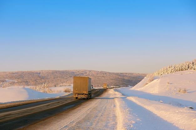 Winterstraße in den bergen. der lkw fährt die straße entlang Premium Fotos