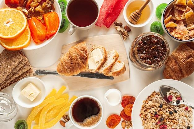 Wintervitaminfrühstück auf einem weißen tisch. frühstück für zwei personen mit müsli, obst und trockenfrüchten. episches frühstück. extra breites banner. hochwertiges foto Premium Fotos