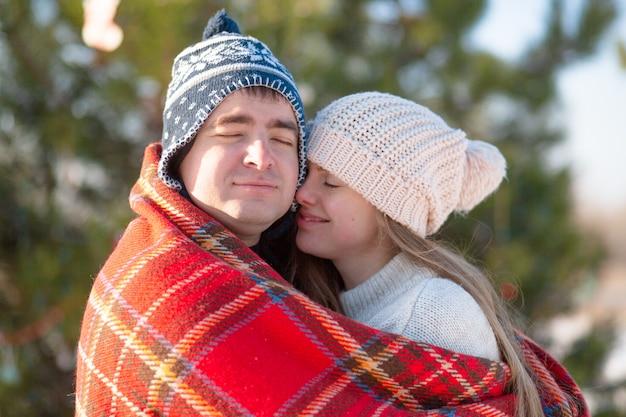 Winterwanderung durch den wald. der mann in der roten plaiddecke wickelt das mädchen ein, damit es warm wird Premium Fotos