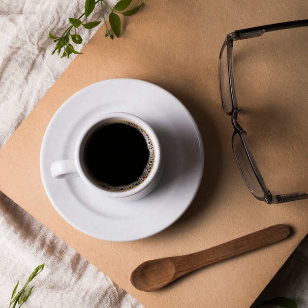 Winzige tasse kaffee auf teller und lesebrille Kostenlose Fotos