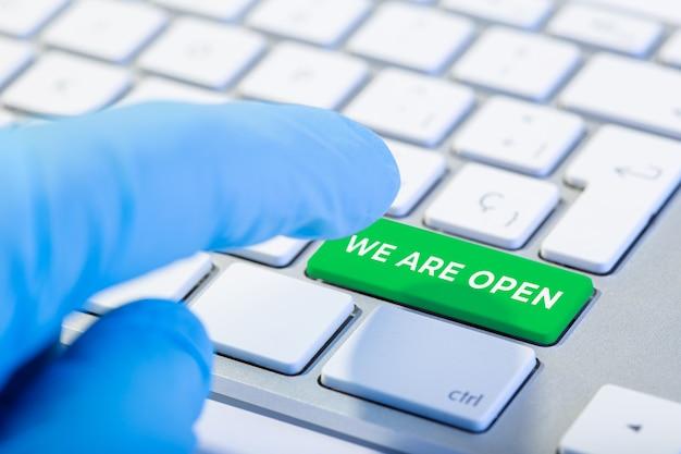 Wir sind offenes konzept. hand mit schutzhandschuh, der eine tastatur mit grüner taste tippt Premium Fotos