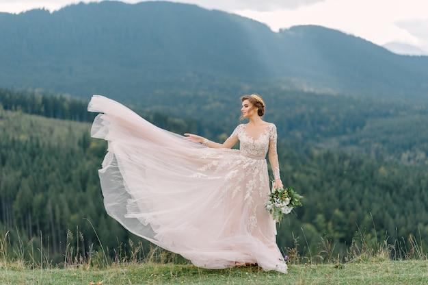 Wirbelnde braut, die schleierrock des hochzeitskleides am kiefernwald hält Premium Fotos