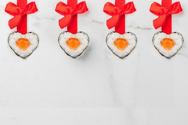 Wirkliche sushi stellten für valentinstag in der form von herzen, mit rotem band und bogen ein. draufsicht des weißen marmorhintergrundkopien-raumes Premium Fotos