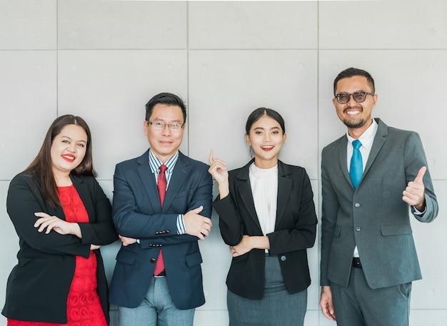 Wirtschaftler, die an in ihrem büro lächeln und stehen Premium Fotos